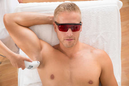 beautiful armpit: Young Man Receiving Laser Epilation Treatment From Beautician At Beauty Center Stock Photo