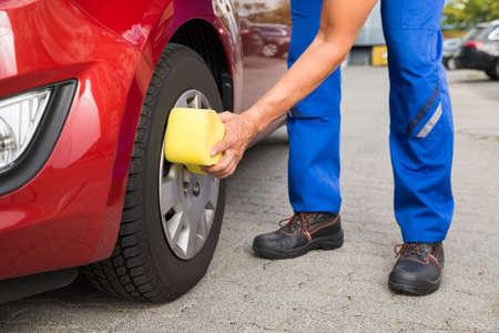 sponge: Mature male worker cleaning car wheel with sponge