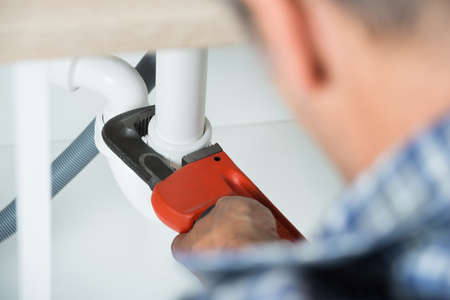 fontanero: Imagen recortada de fontanero tubo disipador de fijación con una llave ajustable en la cocina Foto de archivo