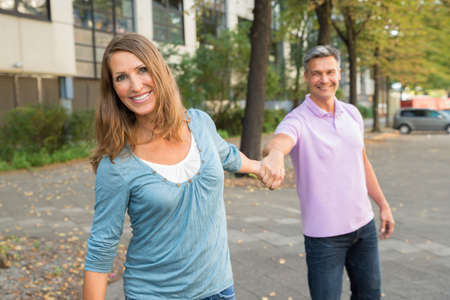 mature man: Happy Mature Man Pulling Woman In The Street