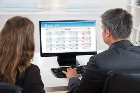 Two Businesspeople Looking At Calendar On Desktop Computer At Desk Stock Photo