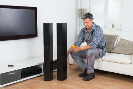 equipo de sonido: Longitud total de la comprobación de altavoces de televisión técnico con el multímetro en el hogar Foto de archivo
