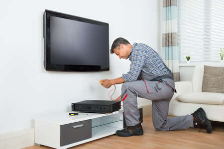 Full length of male technician installing TV set top box at home