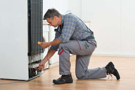 electrical appliances: Full length of technician checking fridge with multimeter at home