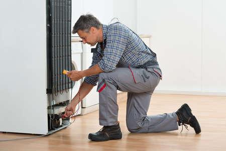 hombres maduros: Longitud total de la comprobación técnico de nevera con el multímetro en el hogar Foto de archivo