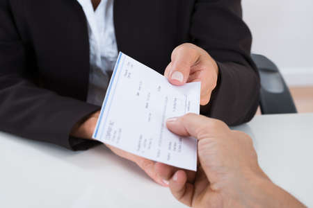 デスクで相手に小切手を与える実業家の手のクローズ アップ