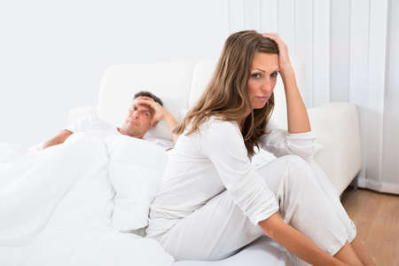 dysfunction: Upset Woman Sitting On The Bed With Man In The Background