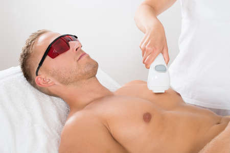 Female Beautician Giving Laser Epilation On Mans Chest