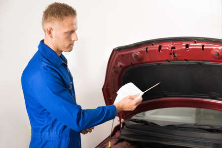 engine bonnet: Close-up Of A Mechanic Checking Oil Level In Car Engine Stock Photo