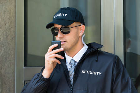 security guard: Retrato de la Guardia de Seguridad joven que usa la radio walkie-talkie
