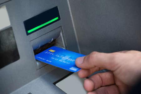 slot machines: Mano del Hombre que usa la tarjeta para retirar dinero