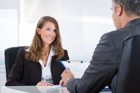 job opportunities: Mature Manager Interviewing A Female Applicant In Office