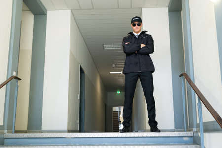 Male Security Guard Standing With Folded Arms At The Entrance Stock Photo