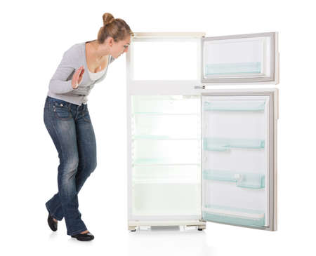 freezer: Full length of young woman looking at empty refrigerator over white background