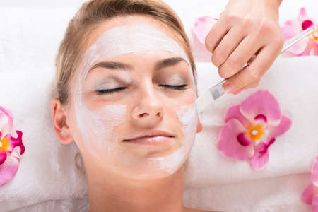peel: Cropped image of beautician applying mask on customers face at salon Stock Photo
