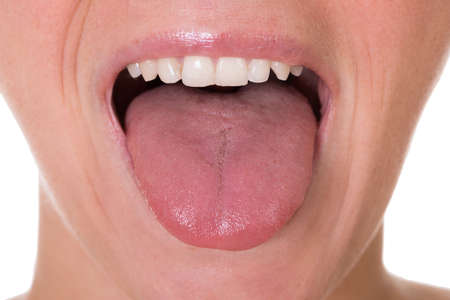 mouth: Cropped image of young woman showing tongue over white background
