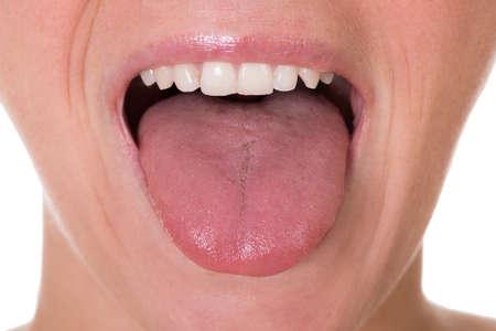 boca abierta: Recorta la imagen de mujer joven que muestra la lengua sobre fondo blanco