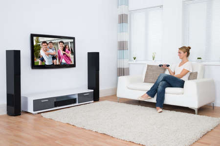 Full length of young woman watching television while sitting on sofa in living room