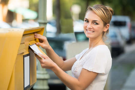 postal: Happy young woman inserting letter in mailbox