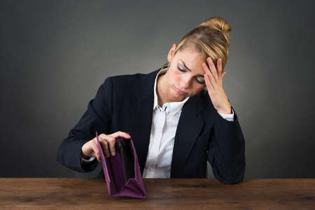 destitute: Sad young businesswoman holding empty purse at desk over gray background