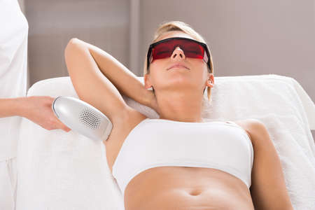 Young woman having underarm laser hair removal treatment in salon Stock Photo