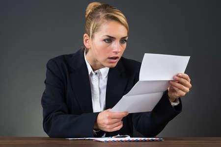 factura: Carta de la lectura de negocios joven sorprendida en el escritorio sobre fondo gris