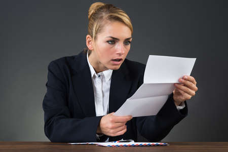 bill: Shocked young businesswoman reading letter at desk over gray background Stock Photo
