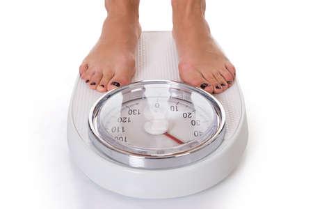 Lage sectie van de vrouw staande op gewicht schaal over witte achtergrond