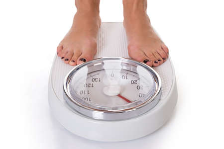 scale weight: Low section of woman standing on weighing scale over white background