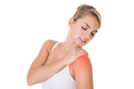 shoulder problem: Sad young woman suffering from shoulder pain over white background
