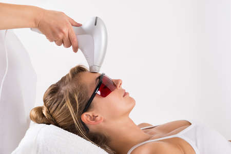 hair and beauty: Closeup of young woman undergoing laser treatment at salon Stock Photo
