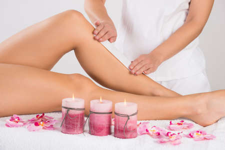 Midsection of beautician waxing womans leg at salon