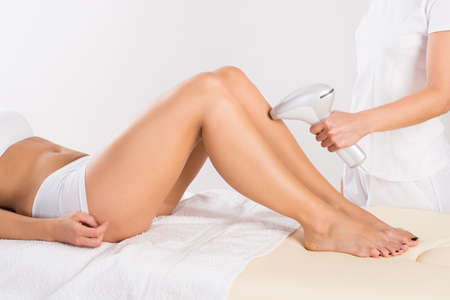 beauty treatment clinic: Midsection of female beautician using laser machine on customers leg at salon