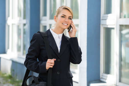 business briefcase: Confident young businesswoman using cell phone while carrying briefcase