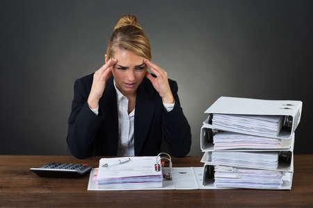 registros contables: Empresaria tensionada masajear la cabeza mientras mira a las carpetas sobre fondo gris Foto de archivo