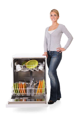 kitchen appliances: Portrait of confident young woman standing arms crossed while leaning on dishwasher over white background