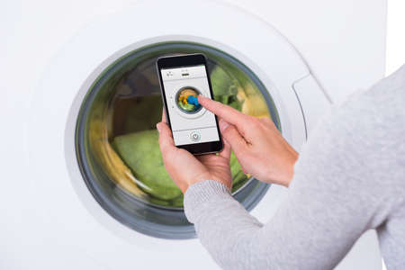 launder: Rear view of young woman using mobile phone to operate washing machine against white background