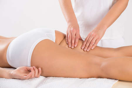 beauty treatment clinic: Midsection of female customer receiving leg massage in salon