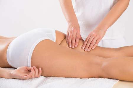 mujer celulitis: Sección media de los clientes de sexo femenino que recibe masaje de la pierna en el salón