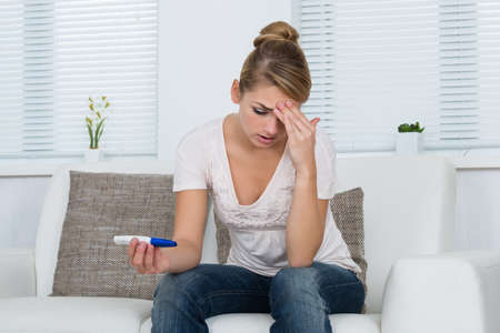 test: Worried young woman looking at pregnancy test while sitting on sofa at home