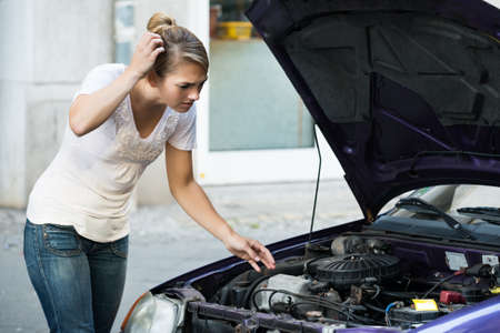 puzzlement: Confused young woman looking at broken down car engine on street Stock Photo