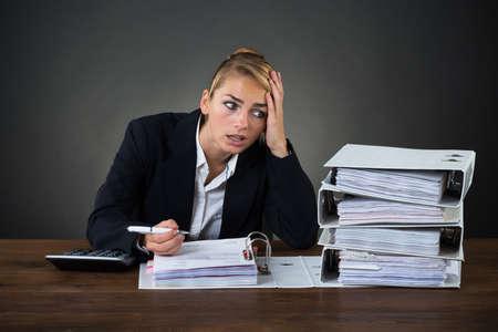 Betonte Gesch�ftsfrau, die Ordner w�hrend der Arbeit am Schreibtisch �ber grauem Hintergrund