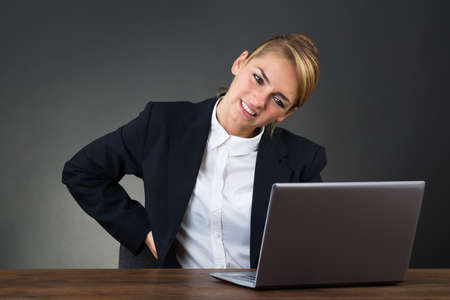 backpain: Young businesswoman suffering from backpain while using laptop at desk over gray background Stock Photo