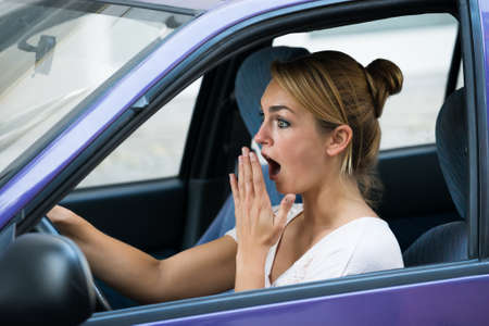 driving a car: Shocked young woman with mouth open driving car Stock Photo