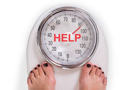 Low section of woman on weight scale with help text over white background