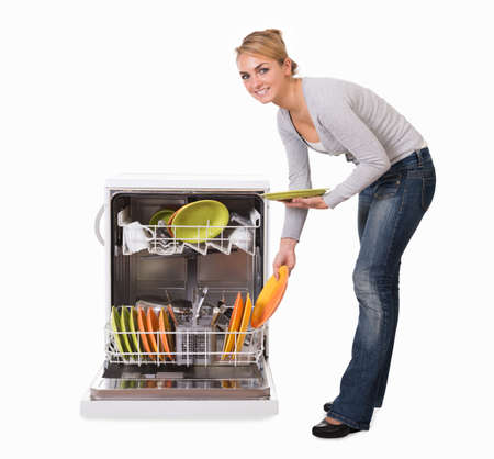over white: Full length side view of young woman arranging utensils in dishwasher over white background Stock Photo