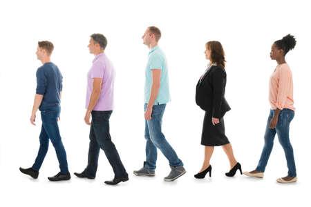 Volledige lengte zijaanzicht van creatieve mensen lopen met de manager in de rij tegen witte achtergrond
