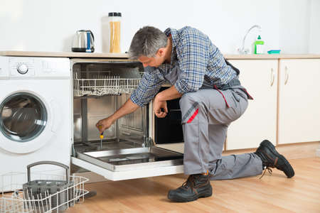 Full length of repairman repairing dishwasher with screwdriver in kitchen Archivio Fotografico