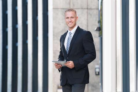 uomo felice: Portrait Of A Young Businessman Looking At Digital Tablet Archivio Fotografico
