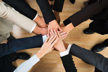 join the team: Directly above shot of business team stacking hands in office Stock Photo